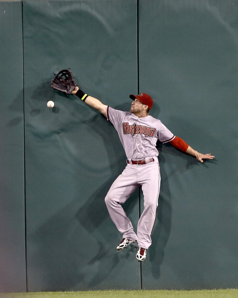 Photo - Arizona Diamondbacks center fielder Ender Inciarte jumps against the wall as he tries to catch the ball hit by Pittsburgh Pirates' Starling Marte for a double that drove in two runs to tie the baseball game in the ninth inning on Tuesday, July 1, 2014, in Pittsburgh. The Pirates scored three runs in the bottom of the ninth inning to win 3-2. (AP Photo/Keith Srakocic)
