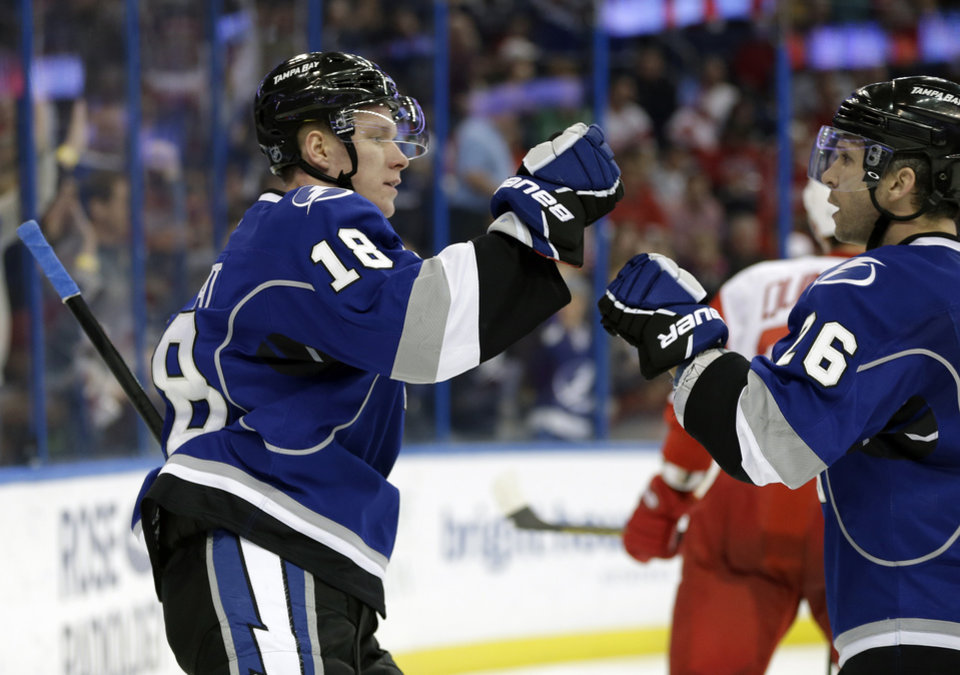 Photo - Tampa Bay Lightning left wing Ondrej Palat (18) celebrates his goal against the Detroit Red Wings with teammate Martin St. Louis (26) during the second period of an NHL hockey game, Saturday, Feb. 8, 2014, in Tampa, Fla. (AP Photo/Chris O'Meara)