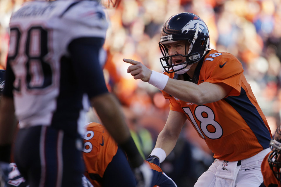 Photo - Denver Broncos quarterback Peyton Manning (18) calls out a play during the second half of the AFC Championship NFL playoff football game against the New England Patriots in Denver, Sunday, Jan. 19, 2014. (AP Photo/Charlie Riedel)