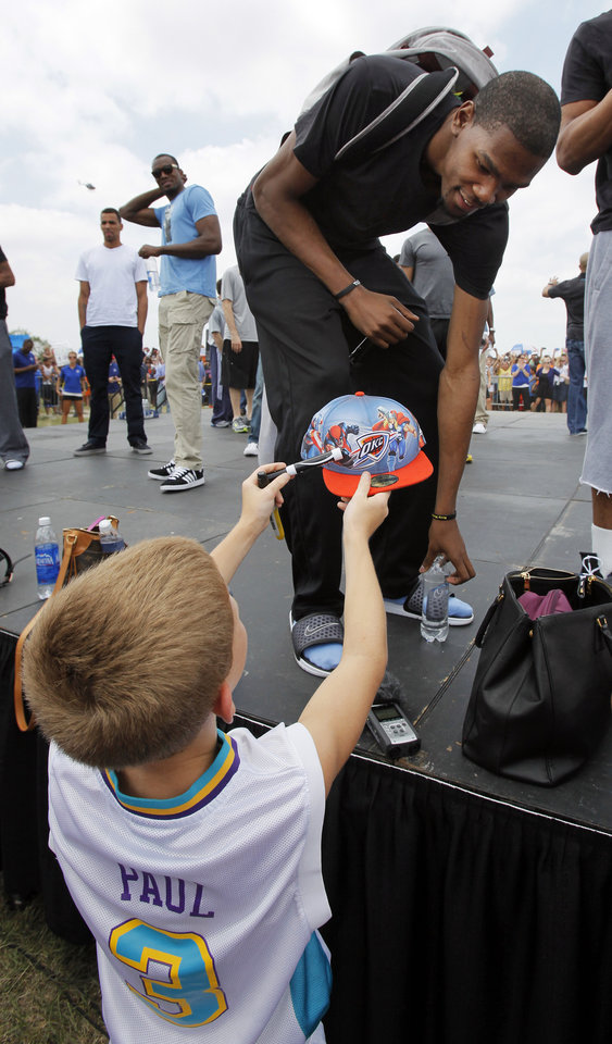 Kevin Durant sets down his bottle of water to autograph a hat during a welcome home rally for the Oklahoma City Thunder in a field at Will Rogers World Airport after the team\'s loss to the Miami Heat in the NBA Finals, Friday, June 22, 2012. Photo by Nate Billings, The Oklahoman