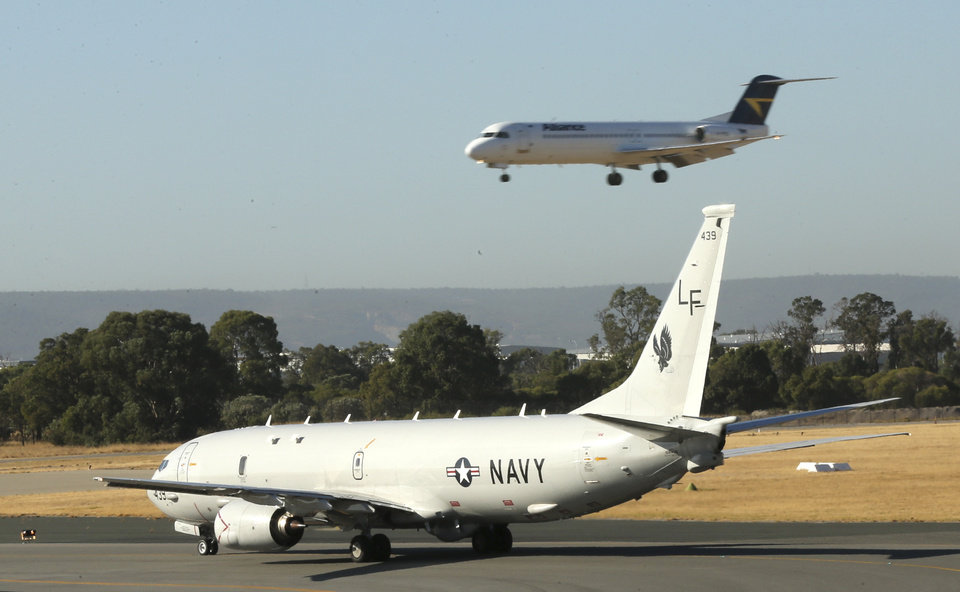Photo - A U.S. Navy P8 Poseidon waits at the end of the runway before it takes off from Perth Airport en route to rejoin the ongoing search operations for missing Malaysia Airlines Flight 370 in Perth,  Australia, Monday, April 14, 2014. The hunt for the missing Malaysian airliner continued to focus Monday on a search for weakening radio signals from deep beneath the waves despite mounting evidence that the batteries in the plane's all-important black boxes may finally have died. (AP Photo/Rob Griffith)