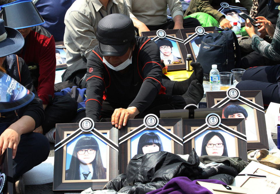 Photo - A family member of the victims of the sunken ferry Sewol displays portraits of victims near the presidential Blue House in Seoul, South Korea, Friday, May 9, 2014. Family members of the victims in the ferry sinking marched to the presidential Blue House in Seoul early Friday calling for a meeting with President Park Geun-hye but ended up sitting on streets near the presidential palace after police officers blocked them. Park's office said a senior presidential official plans to meet them later Friday. (AP Photo/Ahn Young-joon)