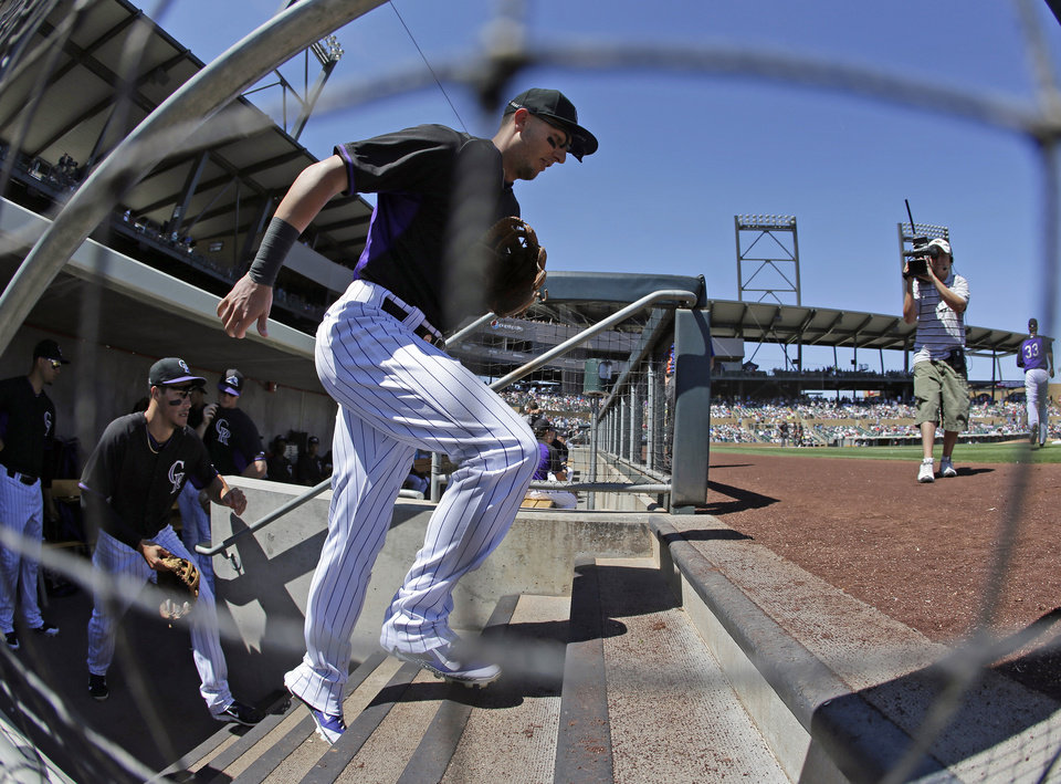 Photo - In this photo taken with a fisheye lens, Colorado Rockies shortstop Troy Tulowitzki runs onto the field for a spring exhibition baseball game against the Seattle Mariners Saturday, March 29, 2014, in Scottsdale, Ariz. (AP Photo/Darron Cummings)