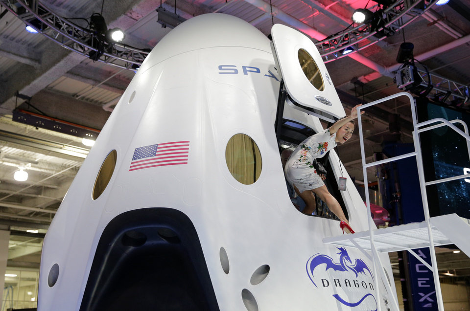 Invited guest Robin Lee walks out of the cabin of the SpaceX Dragon V2 spacecraft at the SpaceX headquarters on Thursday, May 29, 2014, in Hawthorne, Calif. SpaceX, which has flown unmanned cargo capsules to the International Space Station, unveiled the new spacecraft Thursday designed to ferry up to seven astronauts to low-Earth orbit. (AP Photo/Jae C. Hong)
