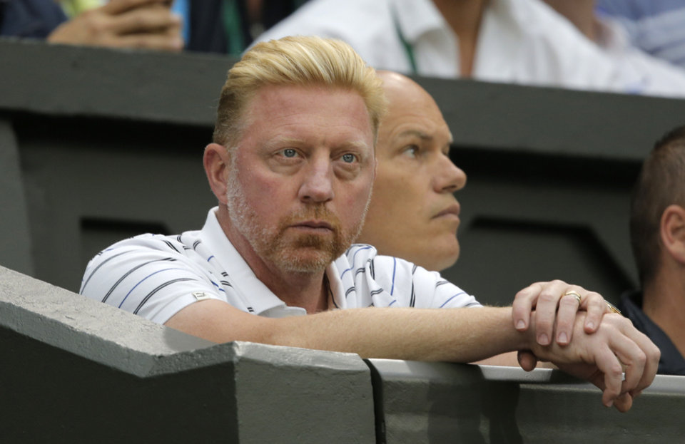 Photo - Former grand slam winner Boris Becker and now coach watches his player Novak Djokovic of Serbia play Jo-Wilfried Tsonga of France during their men's singles match at the All England Lawn Tennis Championships in Wimbledon, London, Monday, June 30, 2014. (AP Photo/Pavel Golovkin)