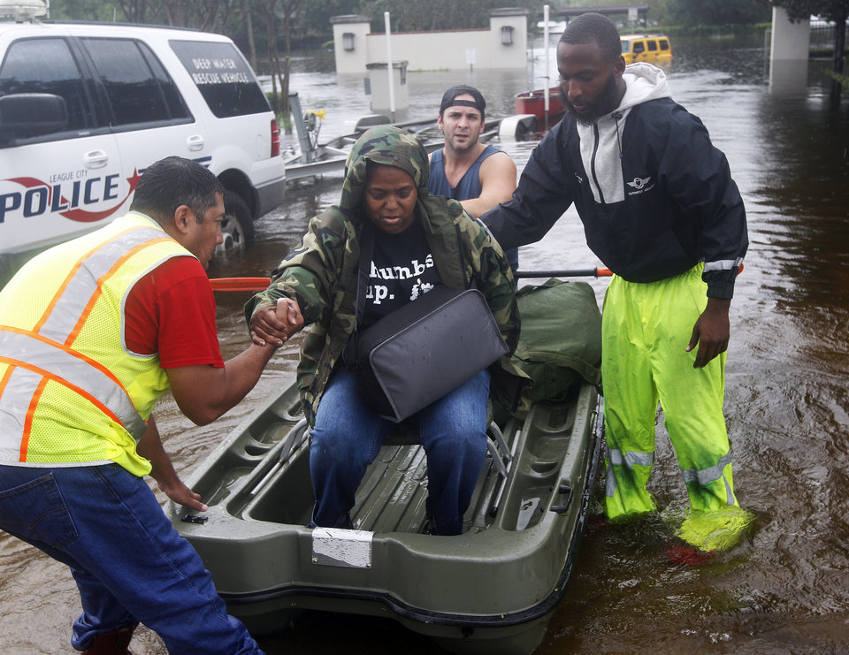 Photo - Janice Hypolite is helped out of flood waters by her son Canan Hypolite, right, and neighbor Mark Goins, rear, after her home in League City, Texas was flooded, Sunday, Aug. 27, 2017. (Kevin M. Cox/The Galveston County Daily News via AP)