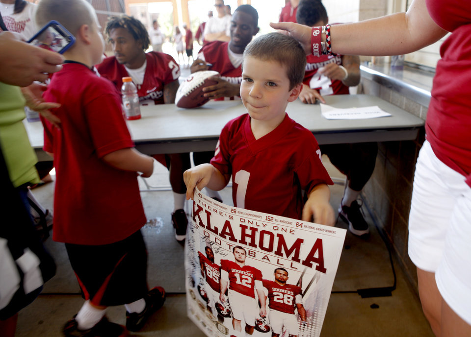 Photo - Kadin Smith, 4, of Lawton walks away after getting an autograph during the University of OKlahoma's Meet the Sooners Day at Gaylord Family-Oklahoma Memorial Stadium in Norman, Okla., Saturday, August 6, 2011. Photo by Bryan Terry, The Oklahoman