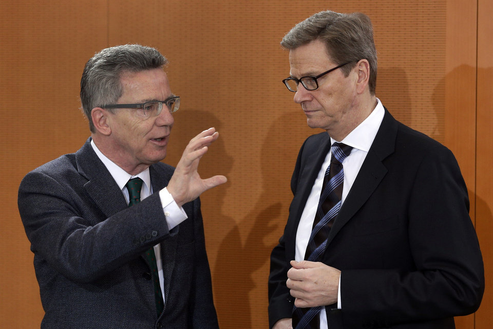 Photo - German Defence Minister Thomas de Maiziere, left, and German Foreign Minister Guido Westerwelle , right, talk as they arrive for the weekly cabinet meeting at the chancellery in Berlin, Germany, Thursday, Dec. 6, 2012. Germany's Cabinet on Thursday approved sending German Patriot air defense missiles to Turkey to protect the NATO member against possible attacks from Syria, in a major step toward possible Western military role in the Syrian conflict. Defense Minister Thomas de Maiziere told reporters that two batteries with a total of 400 soldiers would be sent to the border area under NATO command for one year, although the deployment could be shortened. The decision must be endorsed by the German Parliament, but approval is all but assured.  (AP Photo/Michael Sohn)