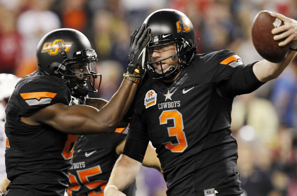 Photo - Oklahoma State's Brandon Weeden (3) celebrates his touchdown against Stanford with teammate Justin Blackmon during the first half of the Fiesta Bowl NCAA college football game Monday, Jan. 2, 2012, in Glendale, Ariz.(AP Photo/Ross D. Franklin)
