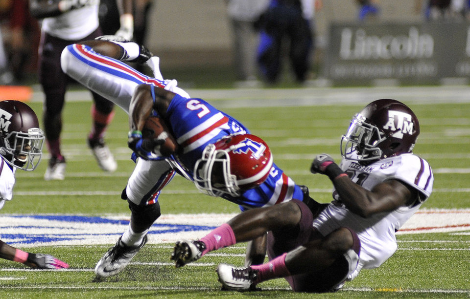 Louisiana Tech's D.J. Banks is slung to the ground by a Texas A&M defender in the third quarter during an NCAA football game in Shreveport, La.,Saturday, Oct. 13, 2012. (AP Photo/Kita K Wright)