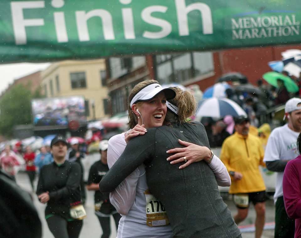 Photo - Valerie Simmons gets a hug from Jackie Roberts (right) as they finish the half marathon during the 11th Annual Oklahoma City Memorial Marathon in Oklahoma City on Sunday, May 1, 2011. Photo by John Clanton, The Oklahoman