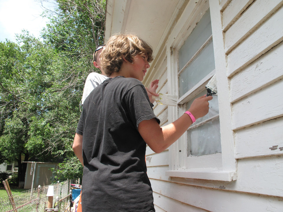 Photo - Brandon DiPaula, 16, from North Church, paints an Edmond home Monday during the servanthood portion of North Church's Love OKC Student Conference.  The Oklahoman - CARLA HINTON
