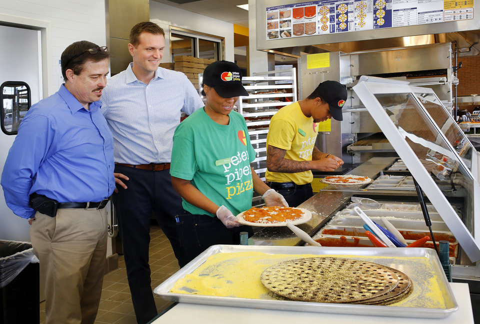 Photo -  Michael Gaines, district manager, left, and Jason Greenwood, chief marketing officer for Peter Piper Pizza, watch employees Sheree Milton and Josh McClain assemble pizzas before placing them into the oven in the company's new restaurant. [Photo by Jim Beckel]