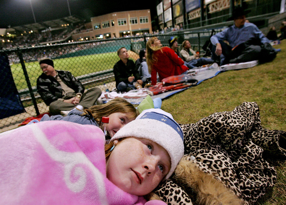 Photo - Madison Hudson, age 9 and her friend Jessica Wilcox, age 9, of OKlahoma City, keep warm under blankets as they watch the Centennial Spectacular on the outfield monitor at the AT&T Bricktown Ballpark in Oklahoma City as part of the State's Centennial celebration. By John Clanton, The Oklahoman