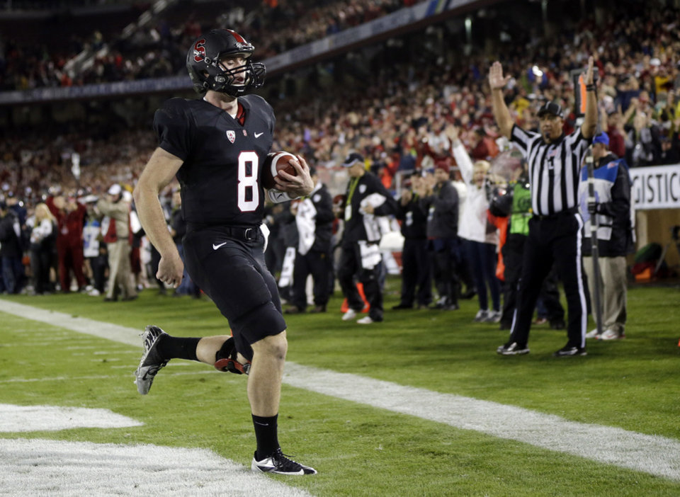 Photo - Stanford quarterback Kevin Hogan scores on a 2-yard run against UCLA during the first half of the Pac-12 championship NCAA college football game in Stanford, Calif., Friday, Nov. 30, 2012. (AP Photo/Marcio Jose Sanchez)