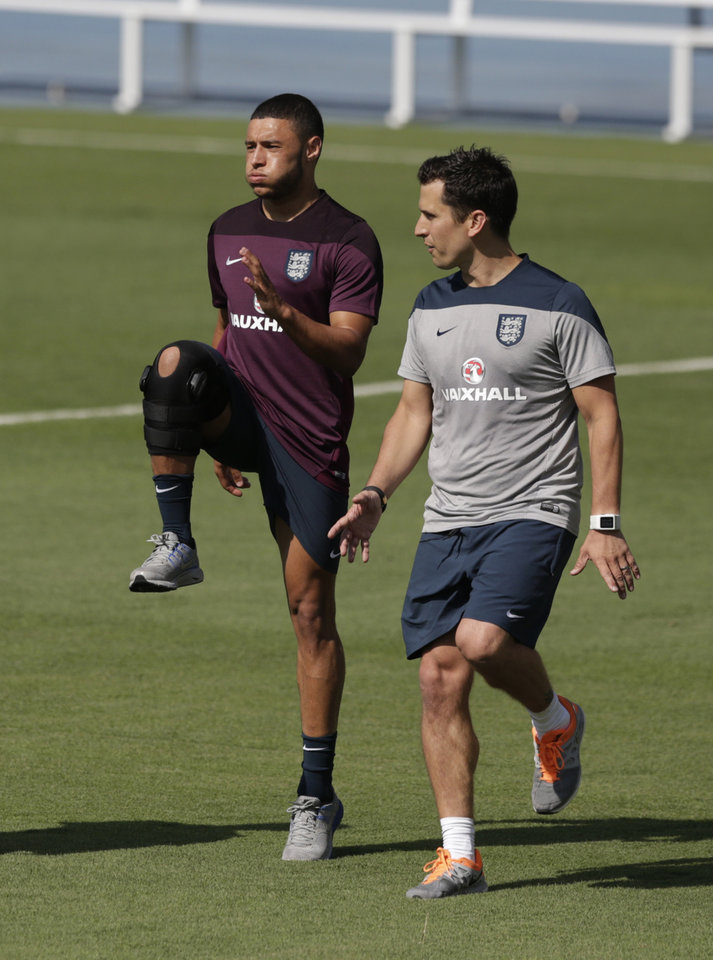 Photo - England's Alex Oxlade-Chamberlain, left, is put through his paces by a member of the coaching staff as he continues to recover from a knee injury during a squad training session for the 2014 soccer World Cup at the Urca military base in Rio de Janeiro, Brazil, Monday, June 9, 2014.  (AP Photo/Matt Dunham)