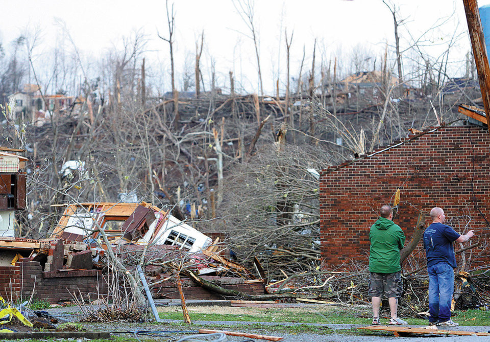 People look at damaged homes on the east side of U.S. 31 in Henryville, Ind., after powerful storms stretching from the U.S. Gulf Coast to the Great Lakes in the north wrecked two small towns and killed at least eight people Friday, March 2, 2012, as the system tore roofs off schools and homes and damaged a maximum security prison. It was the second deadly tornado outbreak this week. (AP Photo/The News and Tribune, C.E. Branham) ORG XMIT: INJEF106