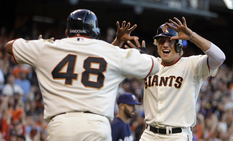 Photo - San Francisco Giants' Hunter Pence, right, and Pablo Sandoval (48) celebrate after scoring against the Milwaukee Brewers in the fourth inning of a baseball game Saturday, Aug. 30, 2014, in San Francisco. Both scored on a double by Michael Morse. (AP Photo/Ben Margot)