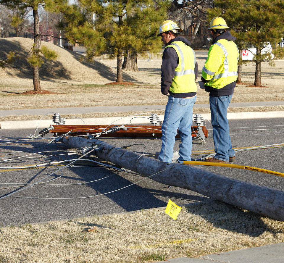 Utility workers view the damage caused by three power poles that fell, one across NE 23rd Street in front of the Governor's Mansion and two across Laird Ave., in Oklahoma City Tuesday, March 26, 2013. Photo by Paul B. Southerland, The Oklahoman