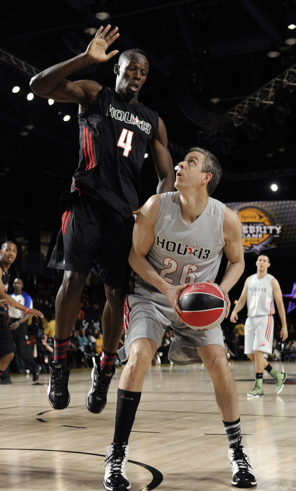 Photo - Olympic gold medal sprinter Usain Bolt (4) towers over U.S. Education Secretary Arne Duncan (26) during the second half of the NBA All-Star celebrity basketball game  Friday, Feb. 15, 2013, in Houston. (AP Photo/Pat Sullivan)