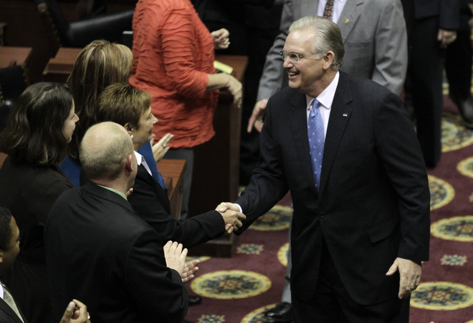 Photo - Missouri Gov. Jay Nixon shakes hands with lawmakers as he enters the House chamber to deliver the annual State of the State address to a joint session of the House and Senate Monday, Jan. 28, 2013, in Jefferson City, Mo. (AP Photo/Jeff Roberson)
