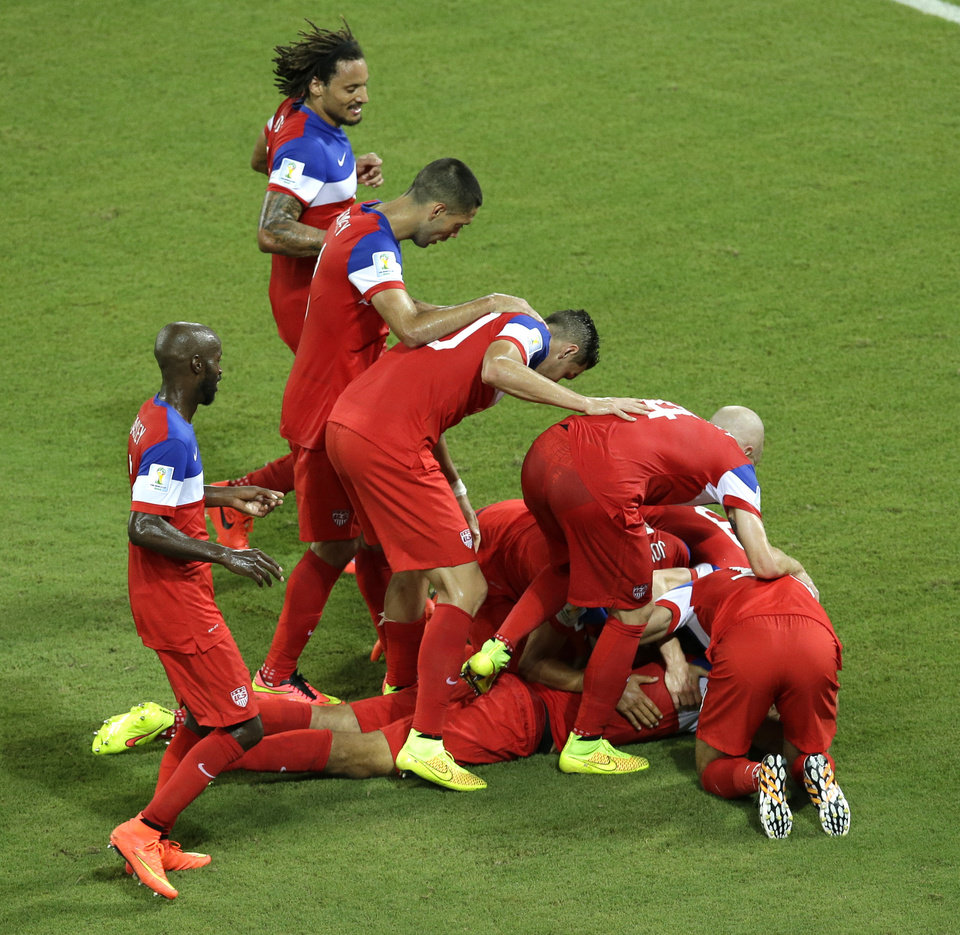 Photo - United States' John Brooks is mobbed by his teammates after scoring their side's second goal during the group G World Cup soccer match between Ghana and the United States at the Arena das Dunas in Natal, Brazil, Monday, June 16, 2014. The United States defeated Ghana 2-1. (AP Photo/Hassan Ammar)