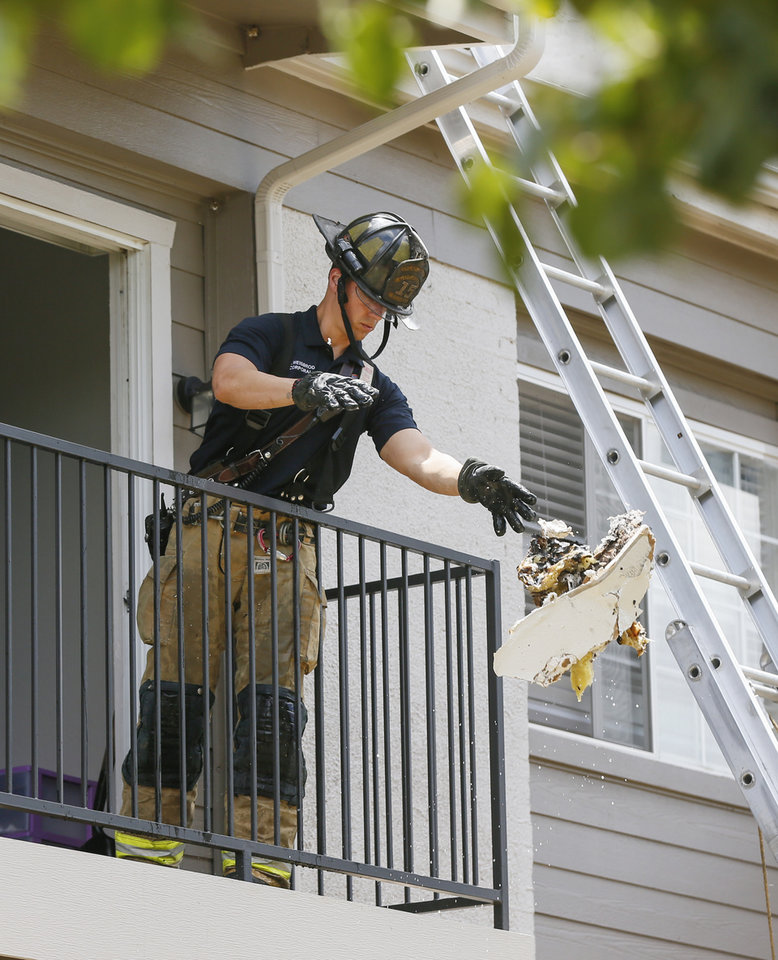 Photo - An Oklahoma City firefighter removes debris from an upstairs unit after firefighters put out an apartment fire in the 7000 block of W Britton Rd. in Oklahoma City, Monday, July 1, 2019. [Nate Billings/The Oklahoman]