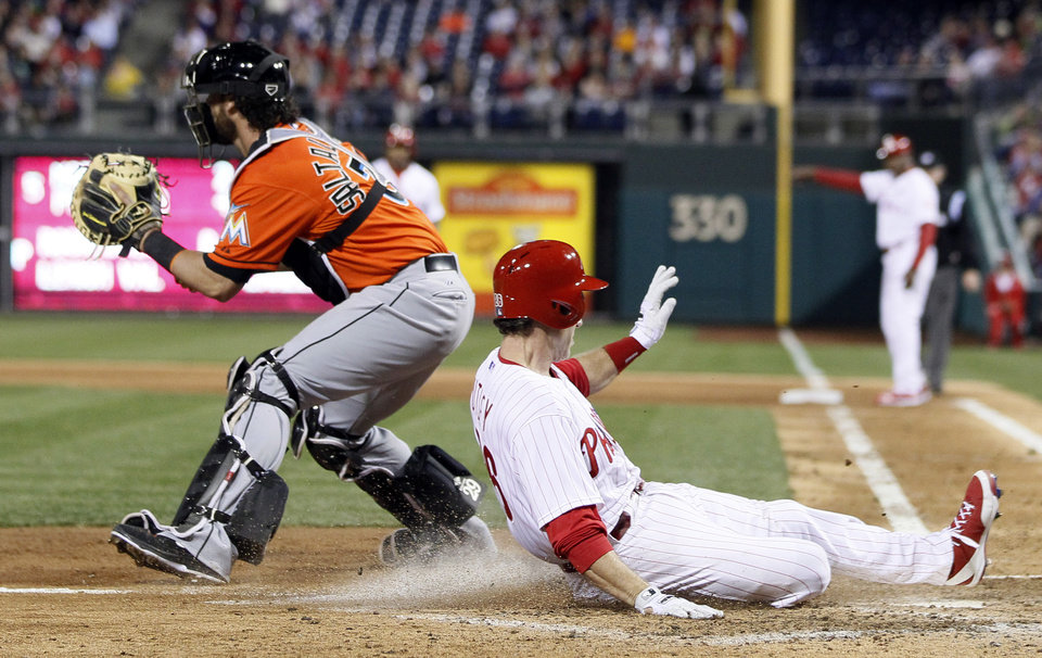 Photo - Philadelphia Phillies' Chase Utley, right, beats the throw to Miami Marlin's Jarrod Saltalamacchia, left, to score from second base on a single by Marlon Byrd during the fifth inning of a baseball game on Friday, April 11, 2014, in Philadelphia. (AP Photo/Tom Mihalek)
