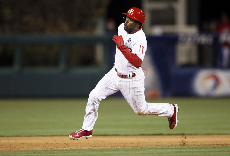 Photo - Philadelphia Phillies' Jimmy Rollins heads to third base hitting triple during the fifth inning of a baseball game against the Miami Marlins, Friday, April 11, 2014, in Philadelphia. (AP Photo/Tom Mihalek)