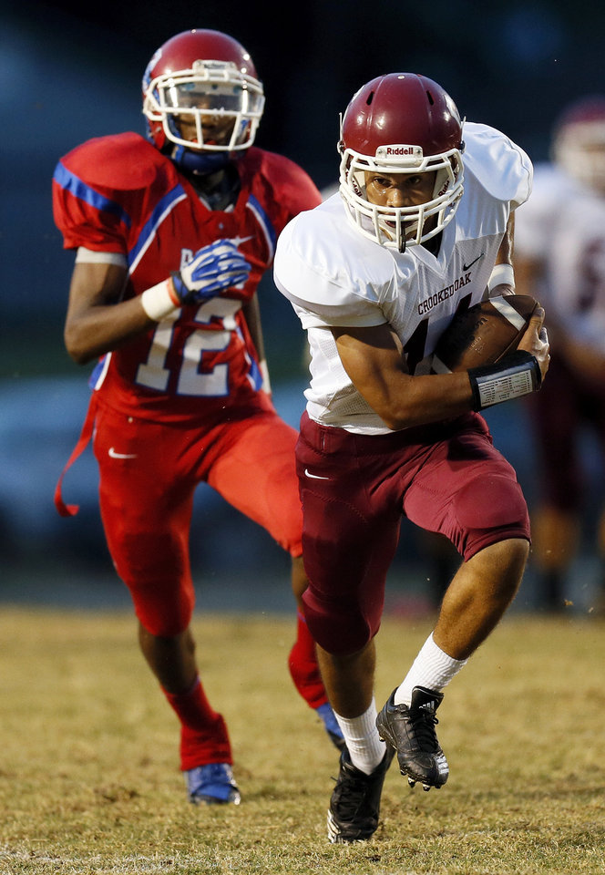 Crooked Oak's DeAndre Kenney (14) runs after a catch from John Marshall's Justin Broiles (12)  during a high school football game between John Marshall and Crooked Oak at Star Spencer's Carl Twidwell Stadium, 3001 NE Spencer Rd., in Spencer, Okla., Thursday, Sept. 19, 2013. Photo by Nate Billings, The Oklahoman