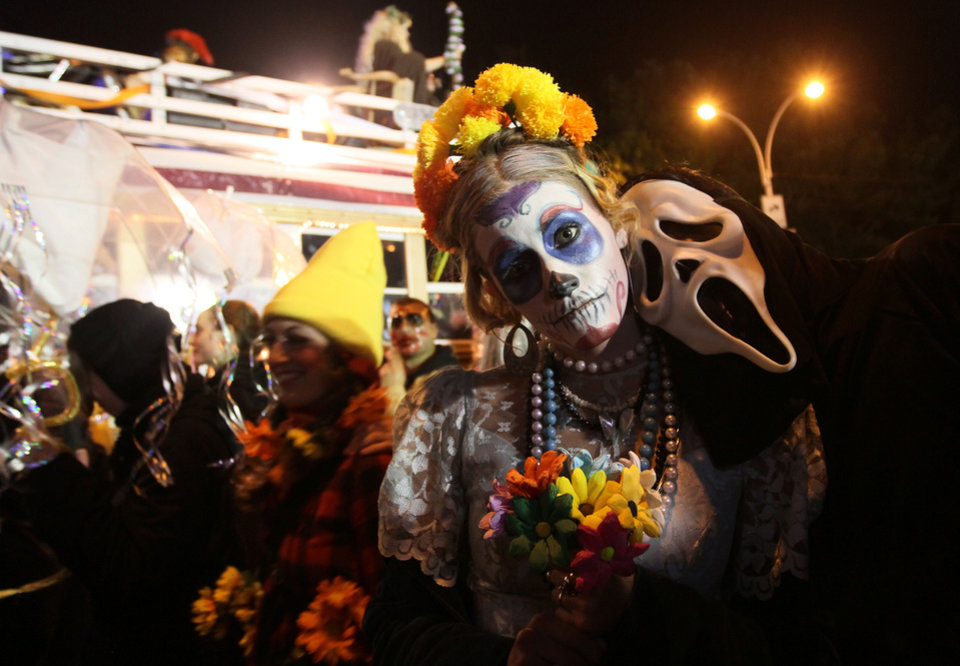 Photo -   FILE - This Oct. 31, 2011 file photo shows costumed participants in the Village Halloween Parade posing for photographs as they make their way up Sixth Avenue in New York. This year's Village Halloween Parade is themed on the end of the world, a reference to a Mayan calendar that ends on Dec. 21. (AP Photo/Tina Fineberg, file)