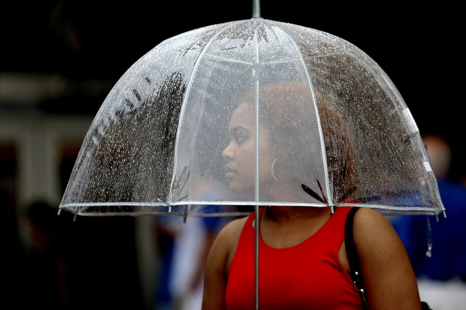 Photo - A fan stands under an umbrella outside the arena before Game 5 in the second round of the NBA playoffs between the Oklahoma City Thunder and the Memphis Grizzlies at Chesapeake Energy Arena in Oklahoma City, Wednesday, May 15, 2013.  Photo by Bryan Terry, The Oklahoman