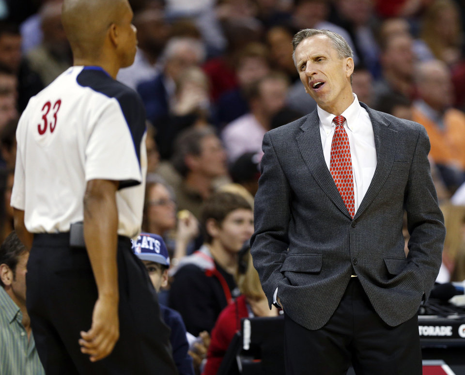 Photo - Charlotte Bobcats head coach Mike Dunlap, right, argues a call with referee Zach Zarba (33) during the second half of an NBA basketball game against the Miami Heat in Charlotte, N.C., Wednesday, Dec. 26, 2012. Miami won 105-92. (AP Photo/Chuck Burton)