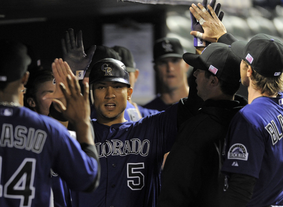 Photo -   Colorado Rockies left fielder Carlos Gonzalez is congratulated by teammates after scoring against the San Francisco Giants during the third inning of a baseball game Tuesday, Sept. 11, 2012, in Denver. (AP Photo/Jack Dempsey)
