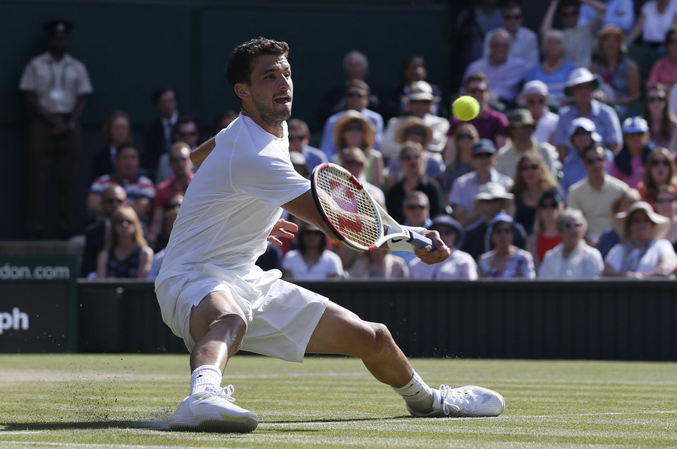 Photo - Grigor Dimitrov of Bulgaria plays a return to Novak Djokovic of Serbia as he falls on Centre Court during their men's singles semifinal match at the All England Lawn Tennis Championships in Wimbledon, London, Friday, July 4, 2014. (AP Photo/Pavel Golovkin)