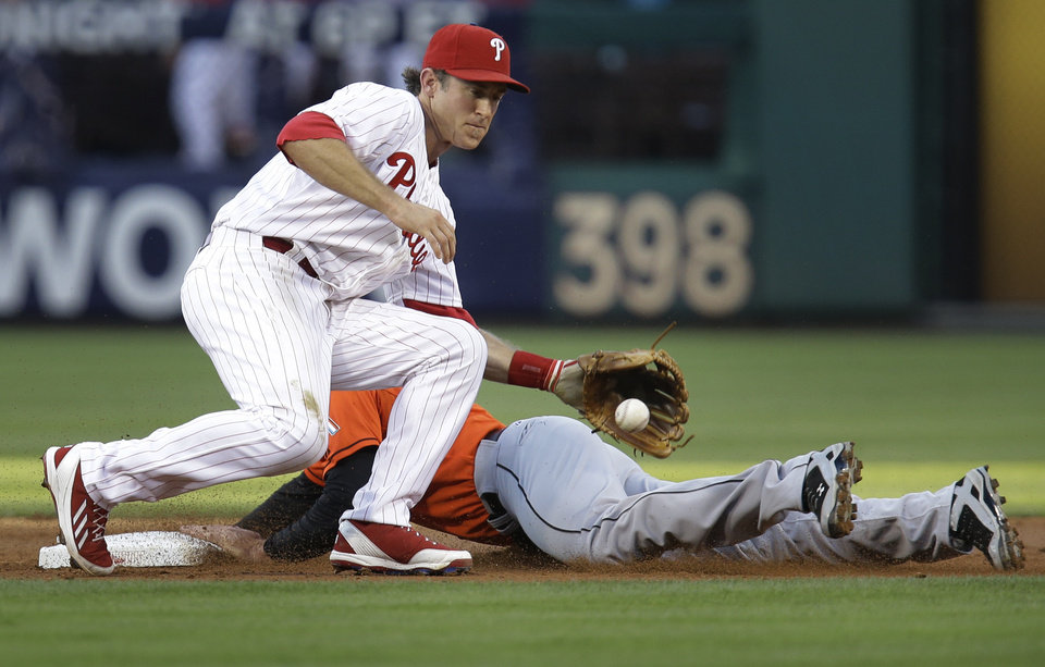 Photo - Miami Marlins' Jake Marisnick is safe on a steal at second before Philadelphia Phillies' Chase Utley can make the tag in the third inning of a baseball game, Thursday, June 26, 2014, in Philadelphia. (AP Photo/Laurence Kesterson)