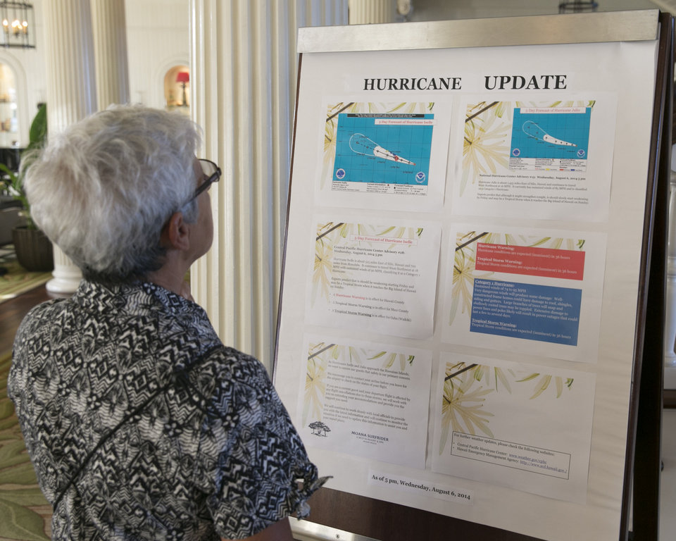 Photo - Tourist Denise Newland of New Zealand reads a hurricane update in the lobby of a hotel in Waikiki in Honolulu on Thursday, Aug. 7, 2014. With Iselle, Hawaii is expected to take its first direct hurricane hit in 22 years. Tracking close behind it is Hurricane Julio. (AP Photo/Marco Garcia)