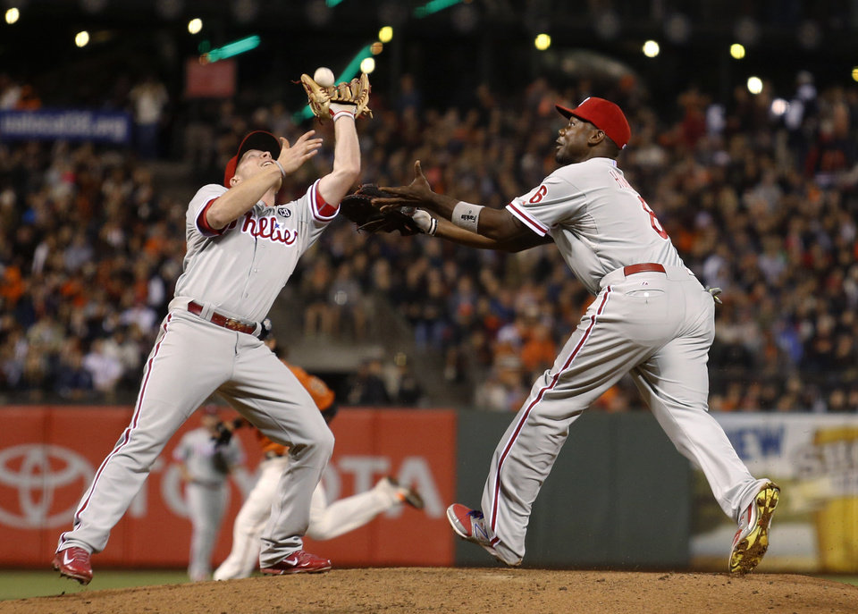 Photo - Philadelphia Phillies first baseman Ryan Howard, right, watches as third baseman Cody Asche catches an infield fly ball hit by San Francisco Giants' Madison Bumgardner to end the sixth inning of a baseball game, Friday August 15, 2014, in San Francisco. (AP Photo/Beck Diefenbach)