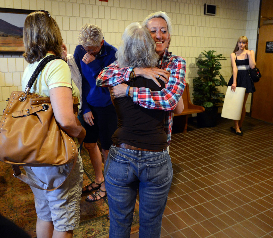 Photo - Supporters of Boulder County Clerk and Recorder Hillary Hall hug outside the courtroom at the Boulder County Justice Center on Wednesday, July 9, 2014 in Boulder, Colo. Hall, is in court to respond to a suit brought by Colorado Attorney General John Suthers who wants the court to issue an injunction to stop the county from issuing marriage licenses to same-sex couples. (AP Photo/Daily Camera, Cliff Grassmick)