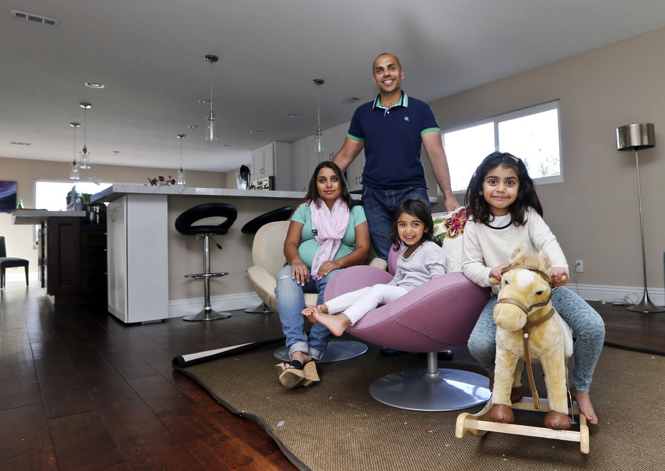 Photo -  The Jaswal family, Imran, standing, his wife Aniqa, left, and daughters, Arissa, right, and Jayda, pose for photos April 16 in the family room at their home in La Jolla, Calif.  AP Photo   Lenny Ignelzi -  AP