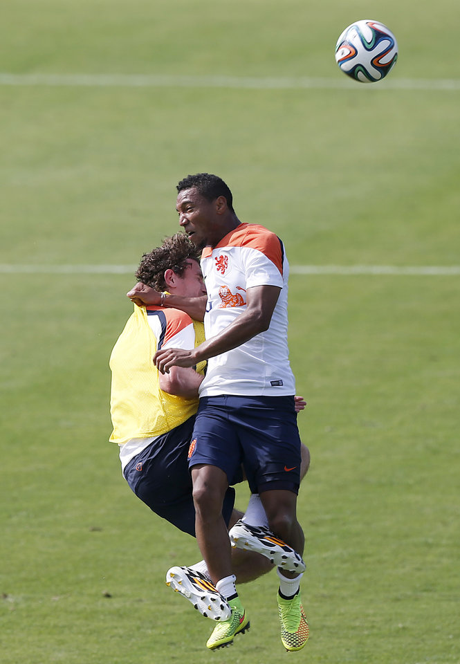 Photo - Jonathan de Guzman, right, and Daryl Janmaat, left, of the Netherlands clash while heading the ball during a training session in Rio de Janeiro, Brazil, Thursday, June 26, 2014.  Netherlands will play Group A runner-up Mexico in the second round on Sunday in Fortaleza. (AP Photo/Wong Maye-E)