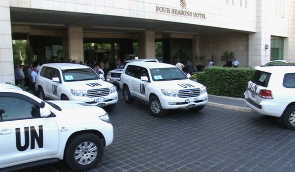 Photo - In this image made from video, U.N. vehicles leave the entry area of a hotel after U.N. weapon inspectors get off their vehicles upon their arrival in Damascus, Syria, Sunday, Aug. 18, 2013. A team of U.N. weapons inspectors arrived in Damascus on Sunday for a long-delayed mission to investigate the alleged use of chemical arms in Syria's civil war. (AP Photo/AP Video)