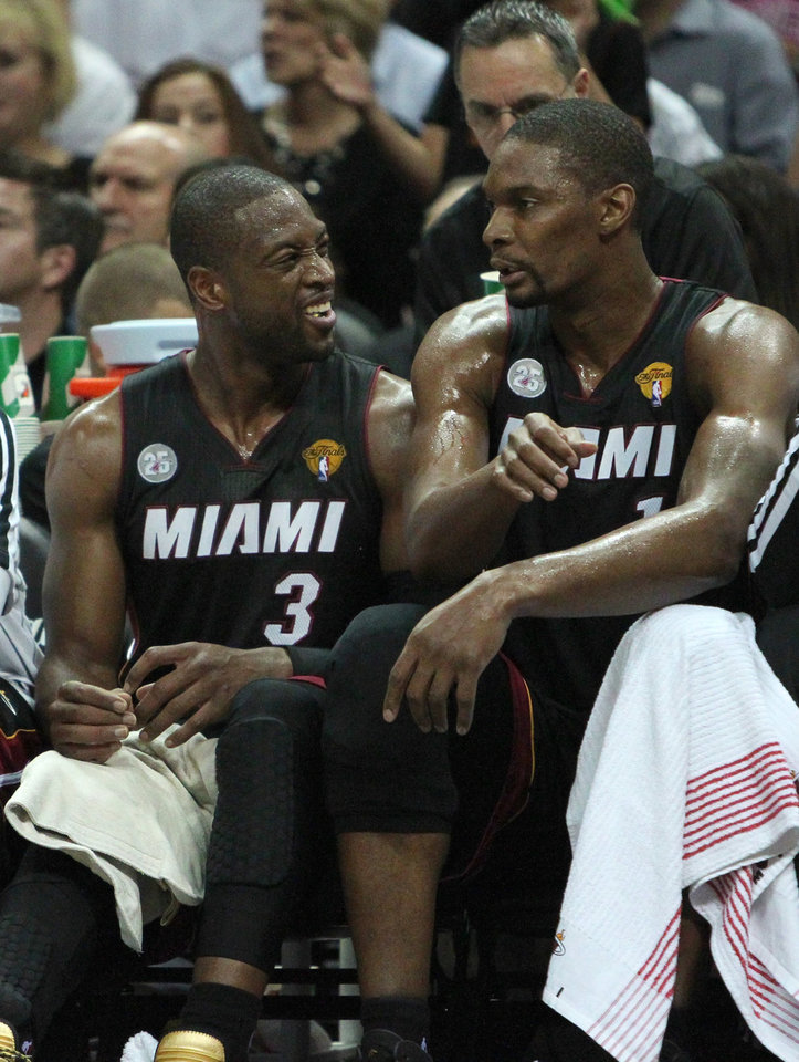 Miami Heat guard Dwyane Wade, left, talks with teammate forward Chris Bosh during the first quarter of Game 4 of the NBA Finals basketball series against the San Antonio Spurs,  Thursday, June 13, 2013, in San Antonio.  (AP Photo/El Nuevo Herald, David Santiago)  MAGAZINES OUT