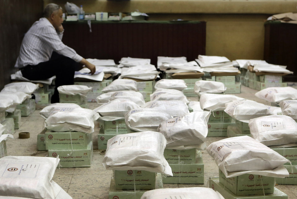 Photo - An Egyptian elections worker guards boxes of ballots at the Giza courthouse in Cairo, Egypt, Sunday, May 25, 2014, a day before the country's presidential elections. Egypt's interim President Adly Mansour has urged Egyptians to come out and vote in this week's presidential election, saying the vote will shape the nation's future. (AP Photo/Amr Nabil)