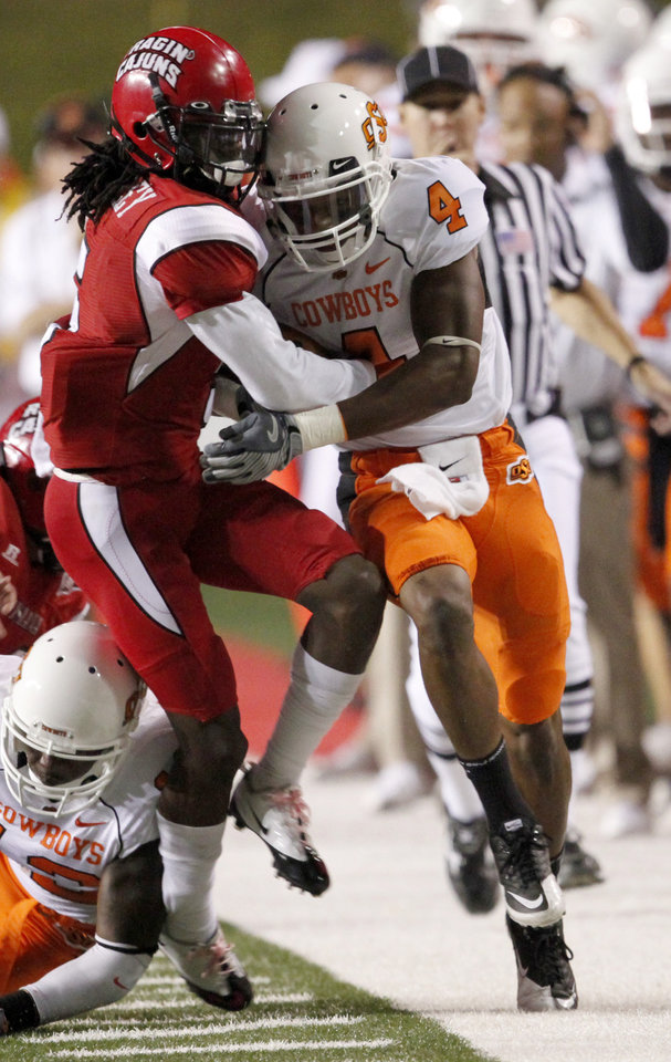 Photo - OSU's Justin Gilbert fights off Louisiana-Lafayette's Dwight Bentley on a return during the football game between the University of Louisiana-Lafayette and Oklahoma State University at Cajun Field in Lafayette, La., Friday, October 8, 2010. Photo by Bryan Terry, The Oklahoman