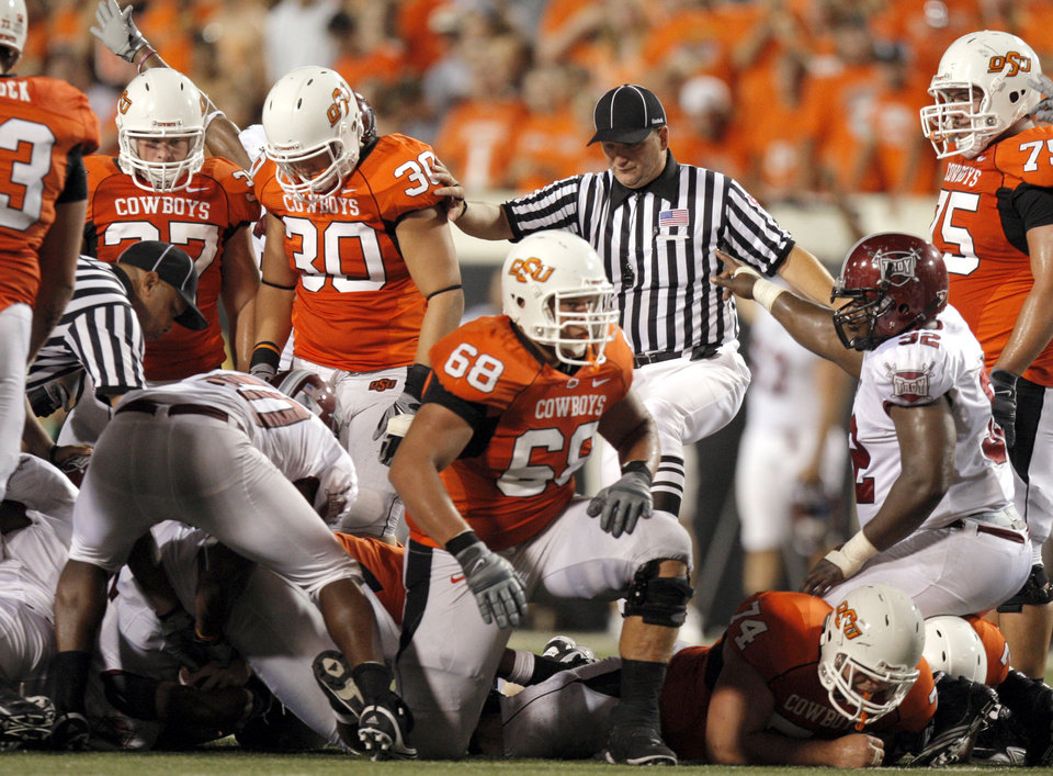 Photo - Officials sort out who recovered a Brandon Weeden fumble as OSU's Lane Taylor (68) gets up from the pile and Troy's Emmanuel Dudley (92) signals Trojan ball during the college football game between the Oklahoma State University Cowboys (OSU) and the Troy University Trojans at Boone Pickens Stadium in Stillwater, Okla., Saturday, Sept. 11, 2010. Photo by Sarah Phipps, The Oklahoman