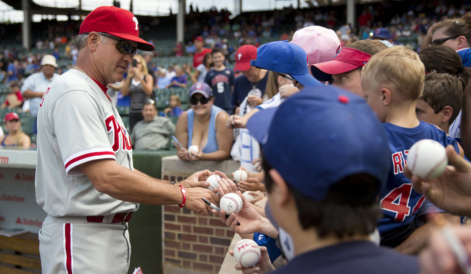 Photo - FILE - In this Aug. 31, 2013 file photo, Philadelphia Phillies interim manager Ryne Sandberg, left,  signs autographs for fans before a baseball game against the Chicago Cubs in Chicago. The celebration of Wrigley Field's 100th anniversary begins Friday, April 4, 2014,  with a visit from an old friend. Sandberg, the Cubs' Hall of Fame second baseman, brings his Phillies to Chicago. (AP Photo/Andrew A. Nelles, File)