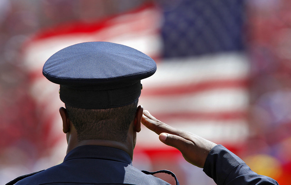 Photo - A Norman police officer salutes the flag before the college football game between the University of Oklahoma Sooners (OU) and the Florida State University Seminoles (FSU) on Sat., Sept. 11, 2010, in Norman, Okla.  Photo by Chris Landsberger, The Oklahoman