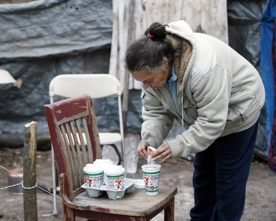 "Photo - Alyce Furr adds cream to coffee brought to her by Barbara Hill at her camp near the North Canadian River in Oklahoma City, Thursday, Dec. 22, 2016. Furr calls herself ""houseless, not homeless."" Hill and others have been helping people at the camp since Hill met Furr in November. Photo by Nate Billings, The Oklahoman"