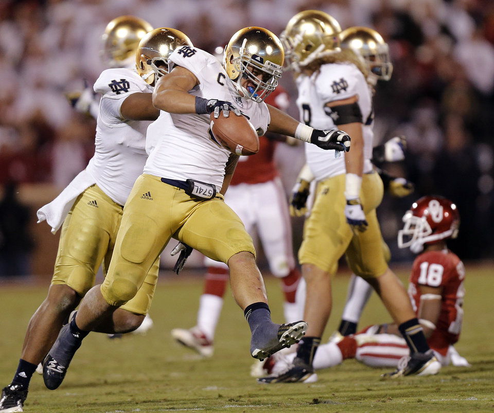 Photo - Notre Dame 's Manti Te'o (5) reacts after making an interception on a pass for OU's Jalen Saunders (18) during the college football game between the University of Oklahoma Sooners (OU) and the Notre Dame Fighting Irish at the Gaylord Family-Oklahoma Memorial Stadium on Saturday, Oct. 27, 2012, in Norman, Okla. Photo by Chris Landsberger, The Oklahoman